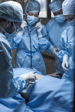 scalpels: Surgical team operating patient