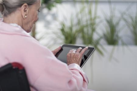 Elderly patient in wheelchair using digital tablet