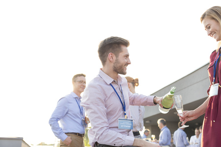 Man pouring champagne into colleagues glass on a company party LANG_EVOIMAGES