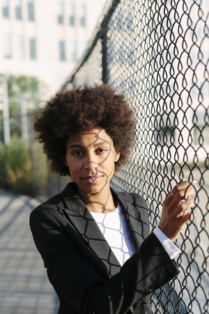 USA, New York City, portrait of businesswoman standing beside mesh wire fence