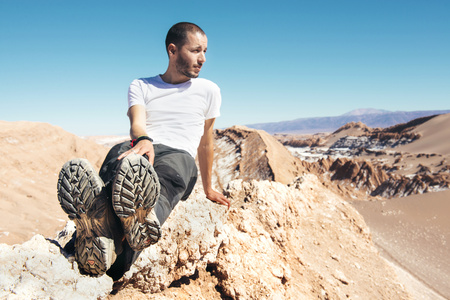 secluded: Chile, Atacama Desert, man sitting on a mountain crest LANG_EVOIMAGES