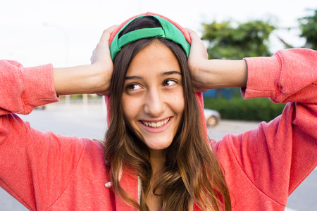 Portrait of smiling girl wearing pink hoodie and basecap
