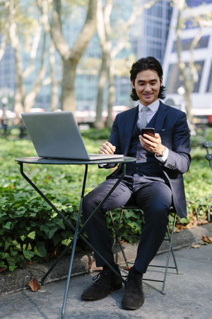 USA, New York City, Manhattan, smiling businessman with laptop and cell phone in Bryant Park