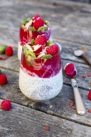 Two glasses of chia pudding with cocos, raspberry sauce and several fruits LANG_EVOIMAGES