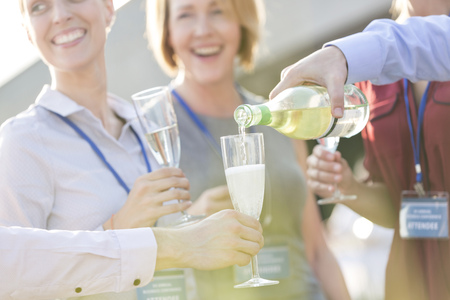 Businessman pouring champagne into glasses on a company party