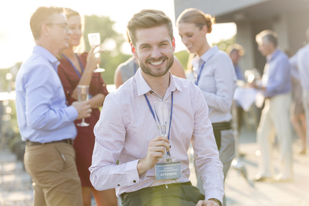 Portrait of smiling businessman holding champagne glass on a company party