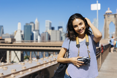 USA, New York City, portrait of smiling young woman with camera standing on Brooklyn Bridge
