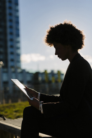 lighted: USA, New York City, silhouette of businesswoman looking at digital tablet LANG_EVOIMAGES
