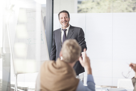 motivations: Laughing businessman at flip chart talking to colleagues