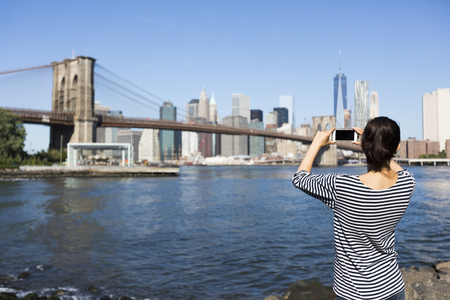 USA, New York City, back view of young woman taking a photo of Brooklyn Bridge with smartphone LANG_EVOIMAGES