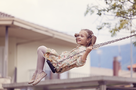 Happy little girl on a swing LANG_EVOIMAGES