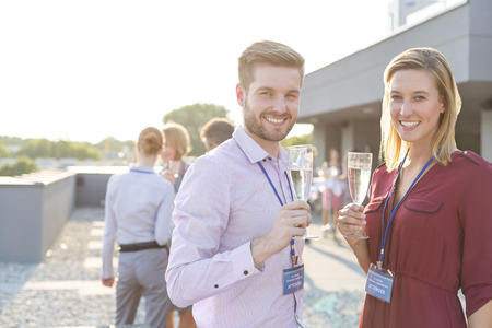 Portrait of two colleagues holding champagne glasses on a company party LANG_EVOIMAGES
