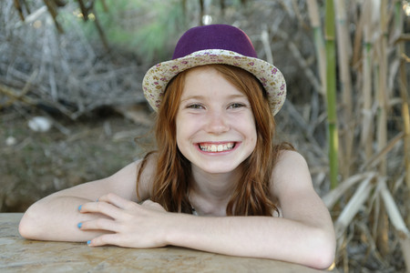 adolescencia: Portrait of grinning redheaded girl wearing hat