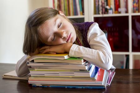 Girl sleeping on stack of school books
