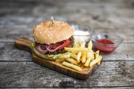 red onions: Homemade burger with lettuce, meat, tomato, onion and french fries on chopping board