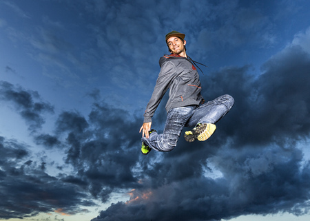 Young man jumping in the air in front of evening sky LANG_EVOIMAGES