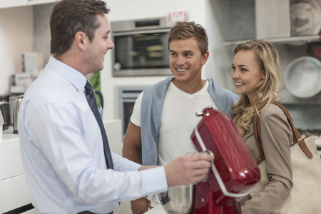 customer facing: Shop assistant talking to young couple shopping kitchen equipment