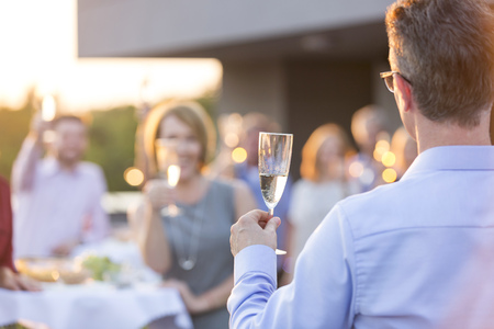 Businessman with champagne glass making a speech on a company party LANG_EVOIMAGES