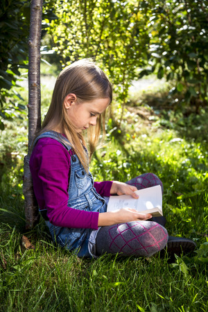 Little girl sitting on a meadow in the garden reading a book
