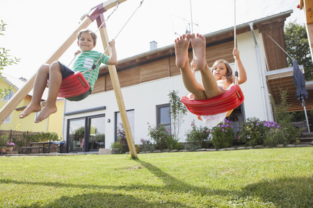 Brother and sister on a swing in garden LANG_EVOIMAGES