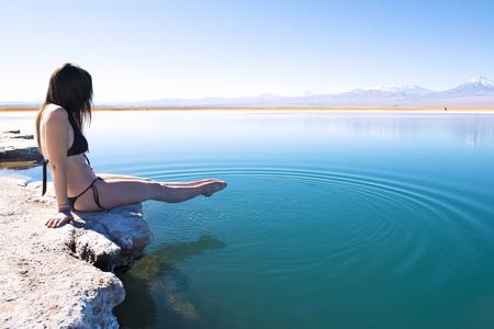 Chile, Atacama Desert, woman in bikini dipping her feet in Laguna Cejar