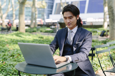 USA, New York City, Manhattan, businessman working with a laptop in Bryant Park LANG_EVOIMAGES