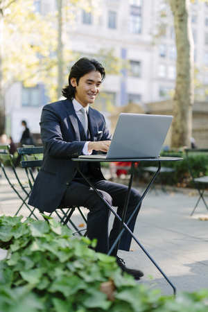 USA, New York City, Manhattan, smiling businessman working with a laptop in Bryant Park LANG_EVOIMAGES