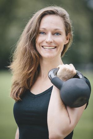levantar peso: Sonriente mujer sosteniendo kettlebell