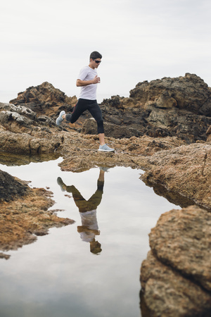 Spain, Ferrol, jogger and his water reflection at the coast