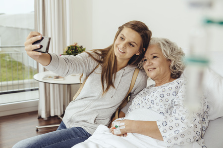 three generations: Granddaughter visiting grandmother in hospital, taking selfie with smart phone LANG_EVOIMAGES
