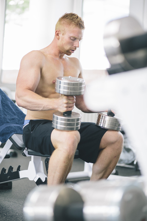 motivations: Physical athlete exercising with dumbbells LANG_EVOIMAGES
