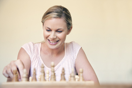 Portrait of woman playing chess LANG_EVOIMAGES