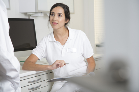 Doctor in medical practice looking at colleague