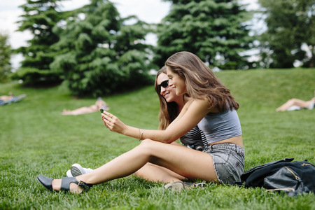 Two happy friends in a park looking at cell phone LANG_EVOIMAGES