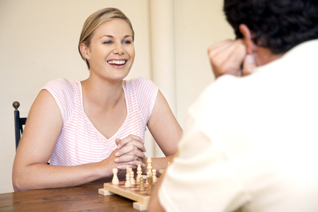 Portrait of woman playing chess with her husband