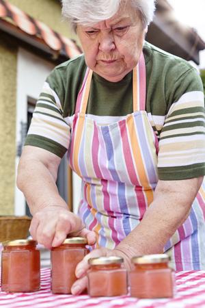 Senior woman closing glass of homemade applesauce