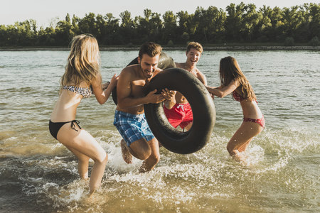 ardor: Playful friends with inner tubes in river LANG_EVOIMAGES
