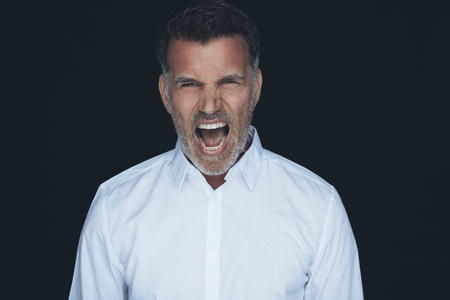 Portrait of screaming man white shirt in front of black background LANG_EVOIMAGES