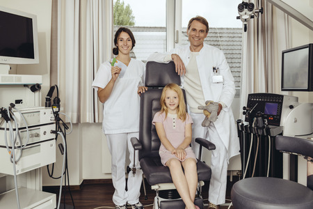 puppets: Doctor and nurse in practice with little girl sitting in  ENT chair