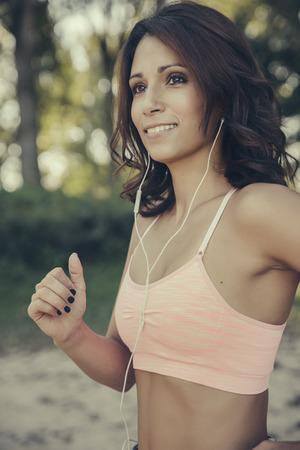 Portrait of smiling woman with earphones jogging