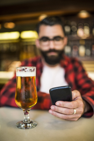 hands free phone: Bearded man sitting in bar, checking emails with beer on counter