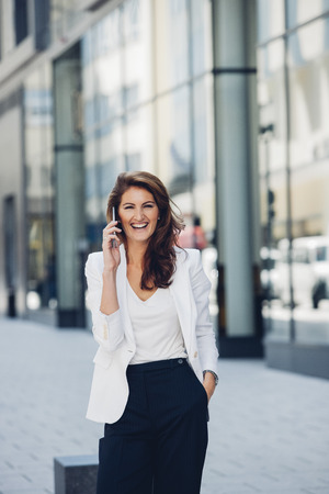 sidewalk talk: Happy businesswoman outdoors on cell phone LANG_EVOIMAGES