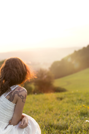 cowering: Germany, Baden-Wuerttemberg, Black Forest, back view of woman on Alpine meadow watching sunrise