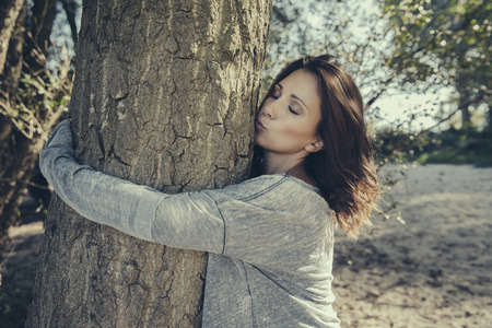 Woman hugging and kissing a tree