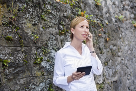 saalfelden: Blond woman standing in front of rock face telephoning with smartphone