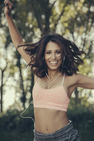Portrait of happy woman with earphones jumping in the air