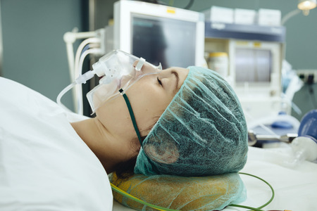 anaesthetic: Narcotized patient with a respiratory mask on operating table