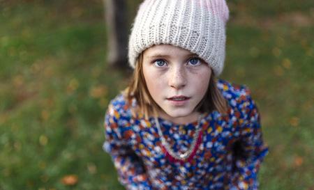 insecurity: Portrait of girl wearing woollen cap looking up
