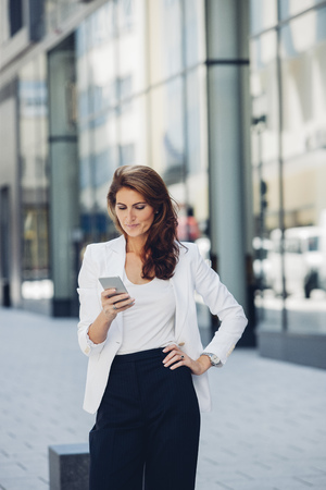 Businesswoman outdoors looking on cell phone LANG_EVOIMAGES