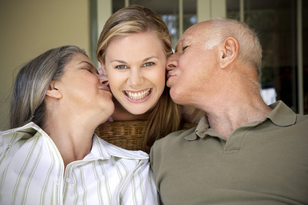 three generations: Portrait of smiling woman with  parents kissing her